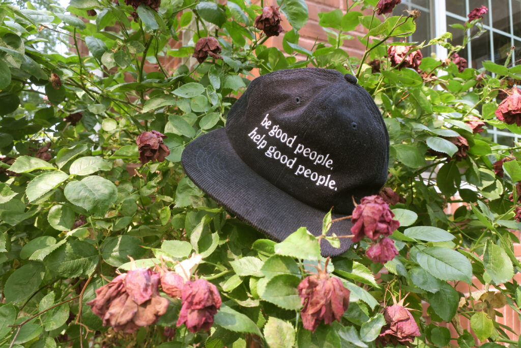 be good people hat laying in a rose bush
